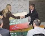 Lina Krištopaitytė imtynininkui Aleksandrui Kazakevičiui įteikia simbolinį 10 000 Lt  čekį