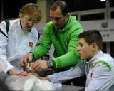 Gydytoja Liudmila Pavlovskaja ir treneris Ruslanas Vartanovas tvarsto turnyro nugalėtojo Kristupo Šleivos traumuotą  pirštą