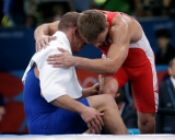Hungary\'s Peter Bacsi is helped off the mat after getting injured in his match against Lithuania\'s Aleksandr Kazakevic during the 74-kg Greco-Roman wrestling competition at the 2012 Summer Olympics, Sunday, Aug. 5, 2012, in London. (AP Photo/Paul Sancya)
